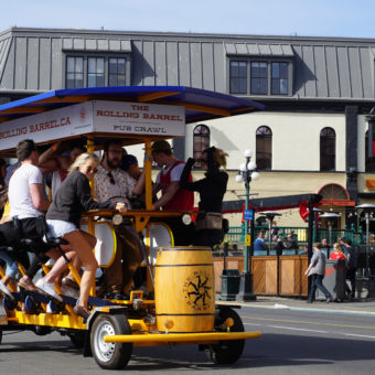 The Rolling Barrel on a summer time tour rolling down Wharf Street in Victoria BC. There is Darcy's Pub in the background!