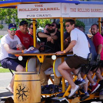 "A group of happy men on tour and pedaling The Rolling Barrel vehicle with ""Captain Mike"" at the helm."