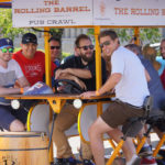 """A group of happy men on tour and pedaling The Rolling Barrel vehicle with """"Captain Mike"""" at the helm."""