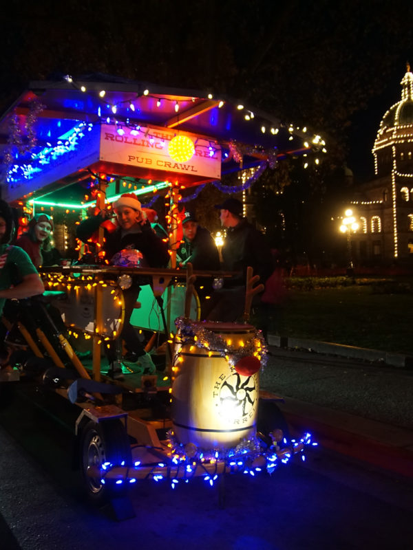Night time front view of the Rolling Barrel vehicle decorated with Christmas lights and parked in front of the Victoria Parliament Building.
